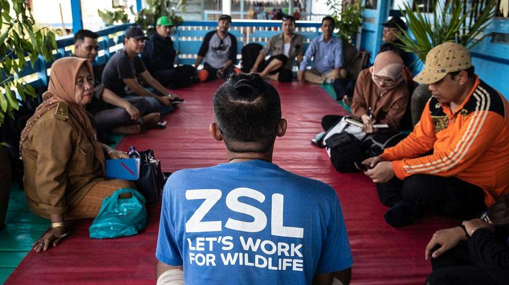 Photo- A group of Indonesian locals and a ZSL representative, sat in a circle having a discussion.