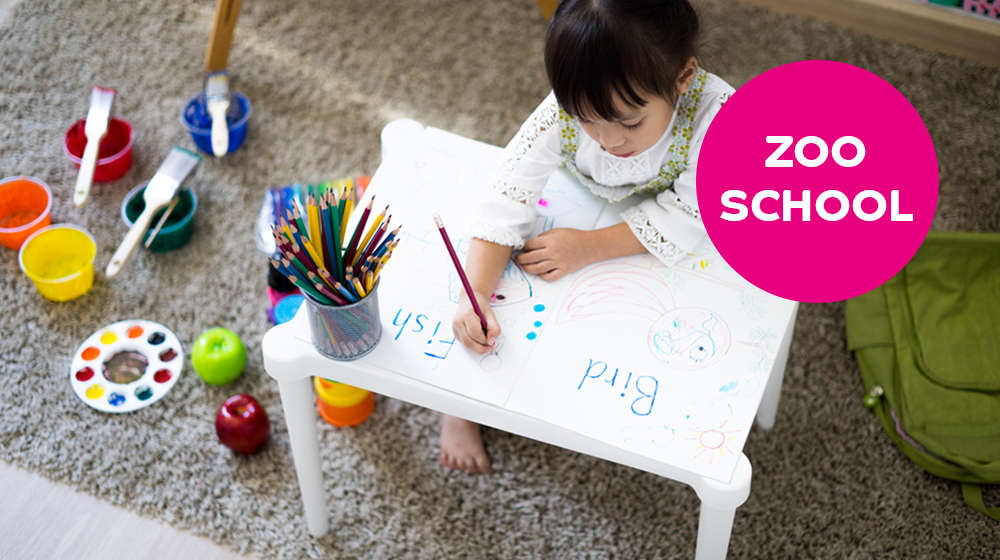 Child sat drawing animals with 'ZooSchool' text