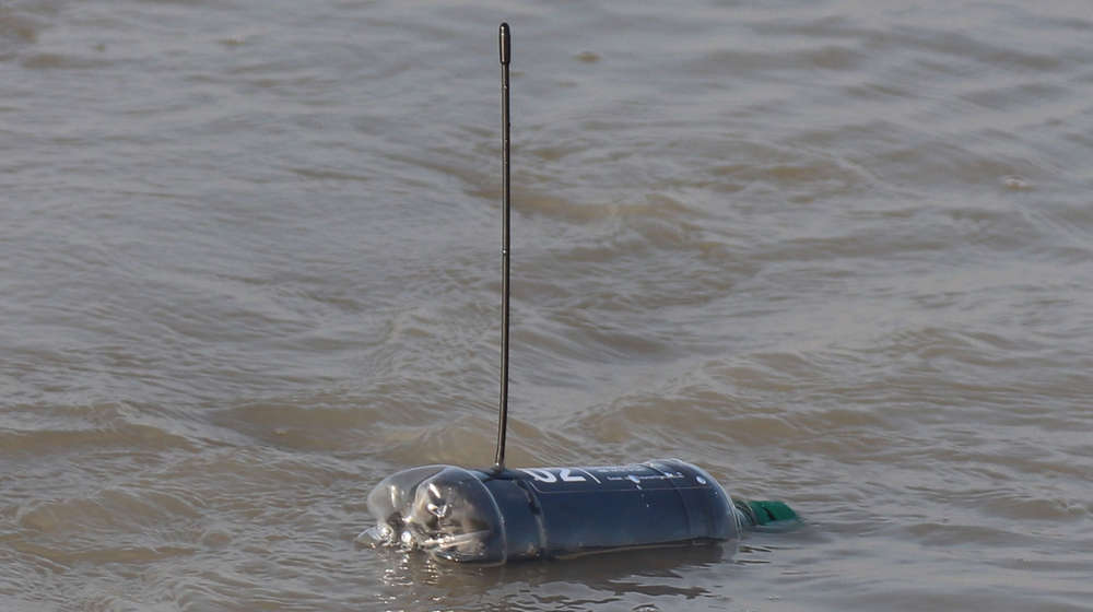A floating plastic bottle with an antennae