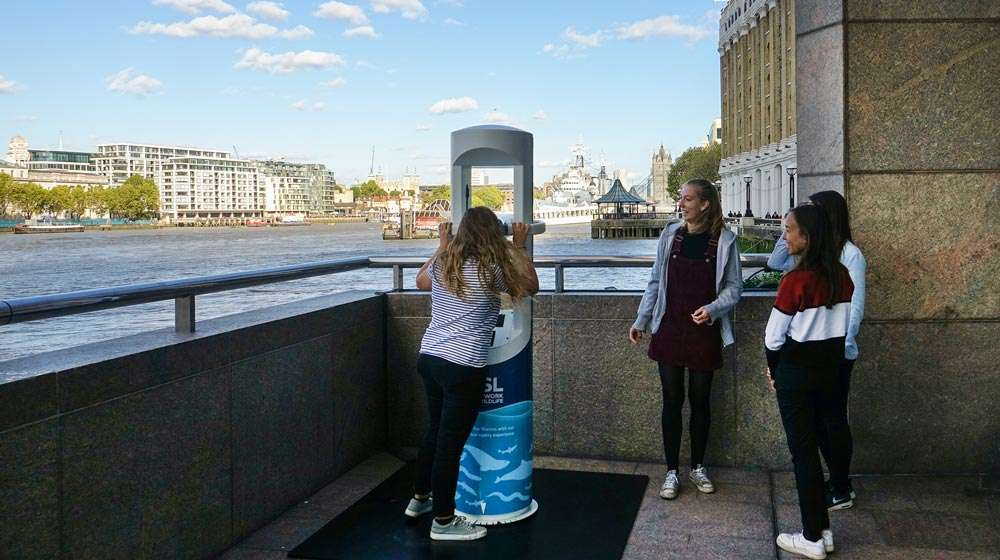 Photo - A girl trying the VR experience while her friends watch, with the Thames and Tower Bridge in the background
