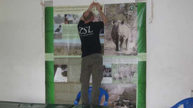 Paul putting a rhino poster on the classroom wall