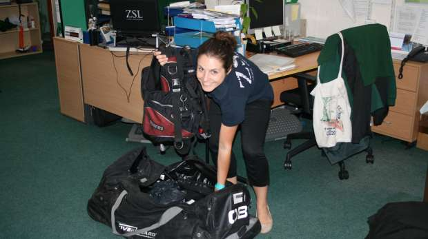 Photo of Ana packing her scuba equipment into her bag
