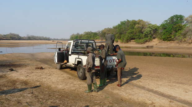 ZAWA scouts changing the flat tyre by the river bank
