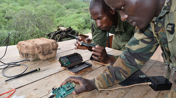 Two men looking at microchips in camouflage gear