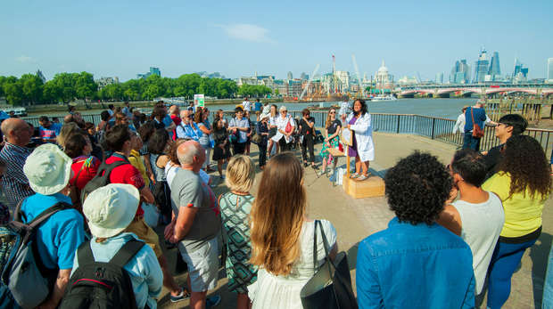 Photo of a Soapbox Science presenter and crowd by the Thames with London skyline in background