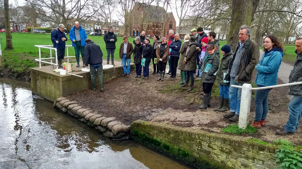 Photo of a group of volunteers by the side of a river next to a village green