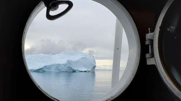 porthole of a boat window with iceberg shown