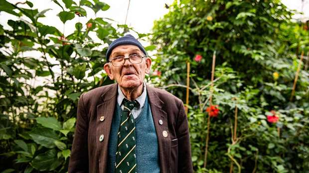 Photo - An older gentleman wearing glasses standing in front of a leafy green bush