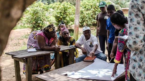 Photo - Members of a local community in Cameroon, outside around a table, having a discussion