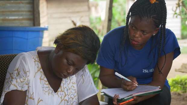 Photo - Two participants of a Village Savings and Loan Association meeting taking notes