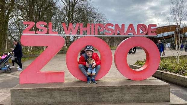 Small boy sits on Whipsnade Zoo sign