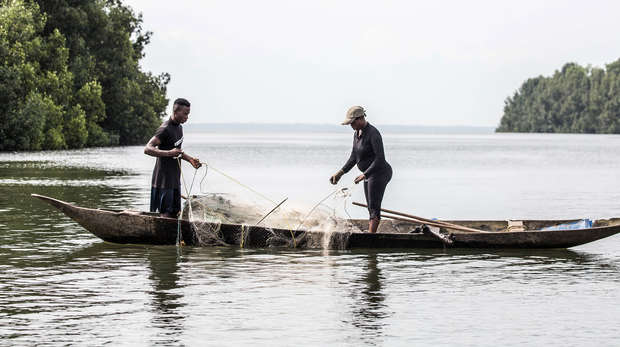 two fishermen stading in a canoe holding nets