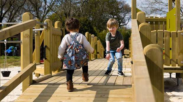 Two pre-schoolers walk towards each other on a wooden play area