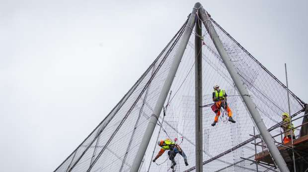 Experts abseil down the Grade II listed Snowdon Aviary to carefully peel away the first of 200 mesh panels