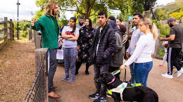 A group of people attending an Audio Described tour at London Zoo