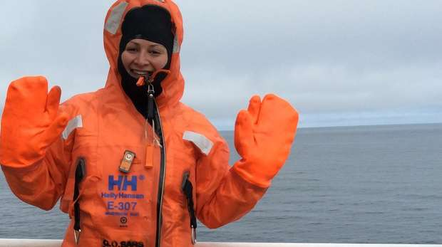 Scientist Emmeline Broad smiles at the camera in a bright orange suit, onboard a research vessel.