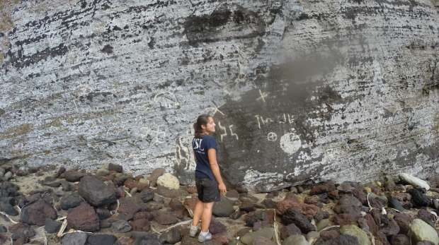 Ana standing by the petroglyphs at Down Rope