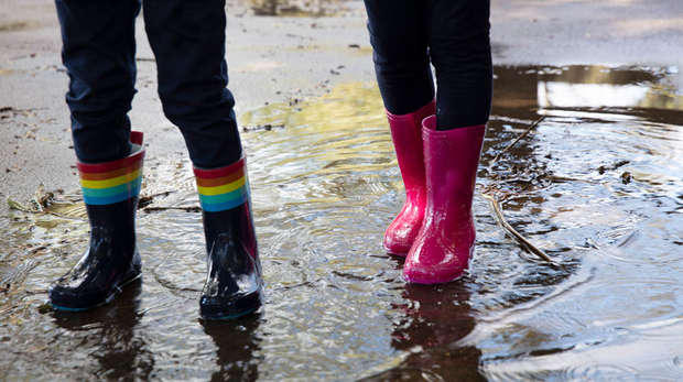 Two children embracing the rain in wellies at ZSL Whipsnade Zoo