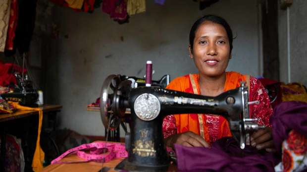 Asian tailor sat at a sewing machine