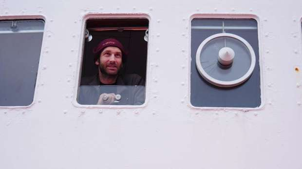 Chris looks out of a window onboard ship