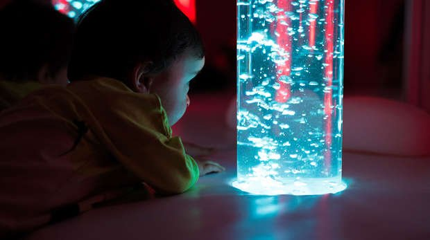 baby looking at lighted water tube