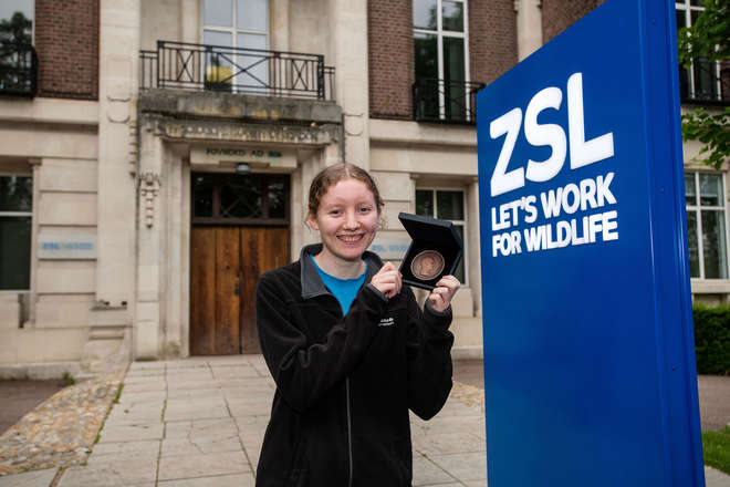 Photo of Mhairi McCann holding up her award, outside the ZSL main building.