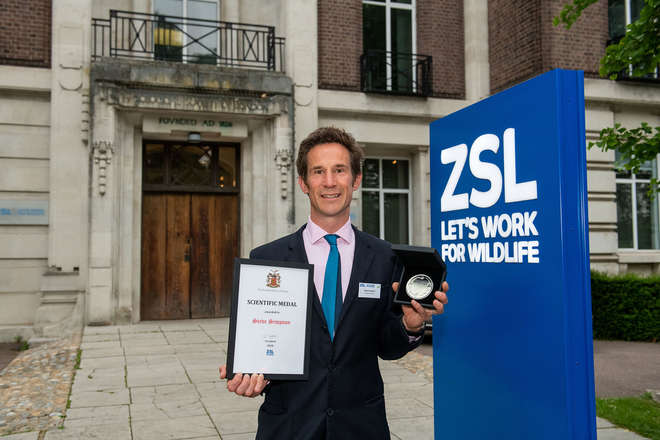 Photograph of Steve Simpson holding up his award, outside ZSL main building