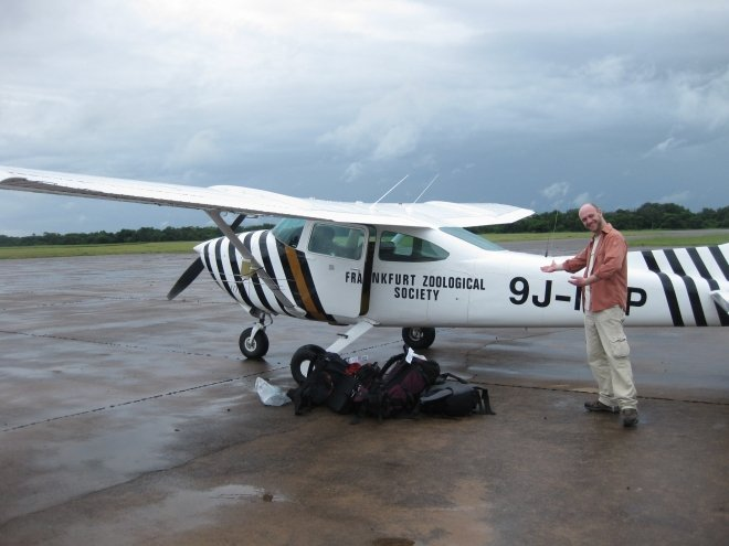 Paul stands next to our tiny zebra-striped plane
