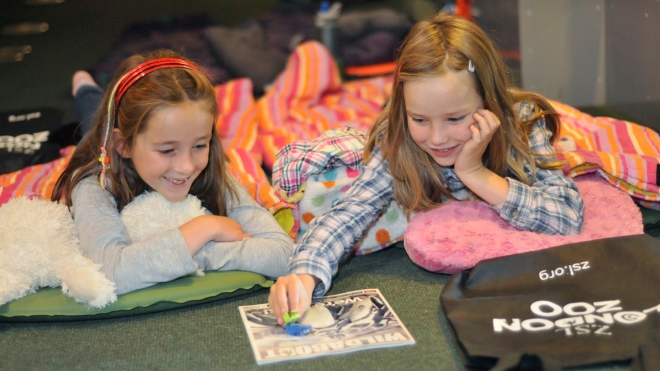 Two girls reading a children's book at BedBUGS!
