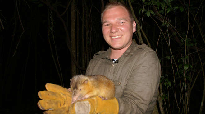 Photograph at night of Sam wearing thick gloves and holding the small mammal