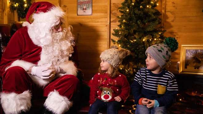 Two children meet father Christmas at ZSL Whipsnade Zoo