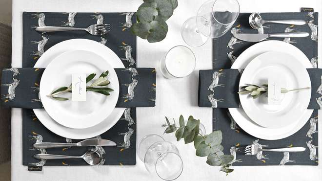 Flaylay of two place settings adorned with eucalyptus leaves and zebra-patterned homewares