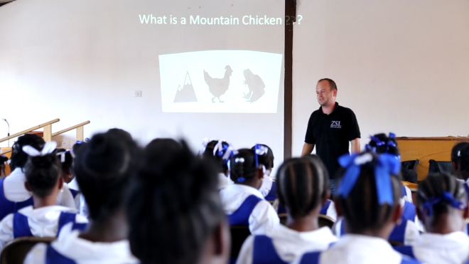 ZSL Conservation volunteer giving a presentation about the mountain chicken frog to school children in Dominica