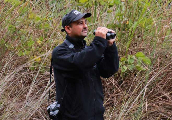 Dr Hem Sagar Barl, ZSL Nepal Country Manager stands in the field with binoculars