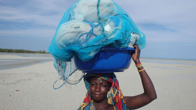 A fisher carrying malaria nets on her head