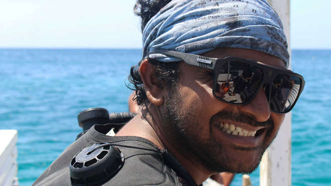 Smiling Ahmed in scuba suit about to investigating coral bleaching in the Maldives