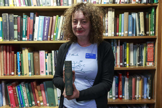 Author of the blog in ZSL Library holding the 1st edition of On the origin of species and wearing a t-shirt showing Darwin's `I think'