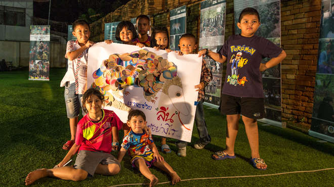 Outdoor group photo of the young children with the poster they've made