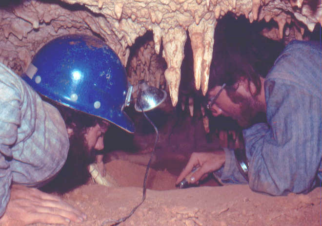 Old photograph of scientists in a cave, uncovering fossils with hand tools