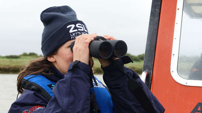 ZSL staff with binoculars on the thames