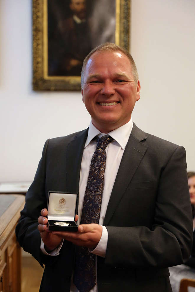 Photograph of Samuel Turvey holding his Linnean medal