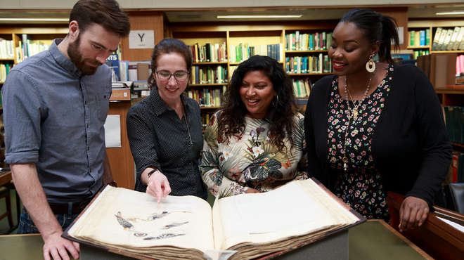 Four people in the library looking at an antique book
