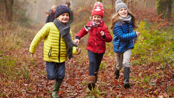 three kids walking in autumn leaves